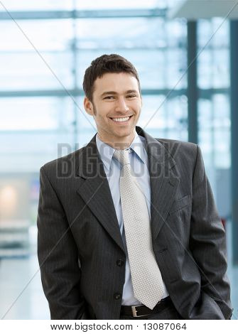Happy businessman standing with hands in pocket in office lobby, looking at camera, smiling.