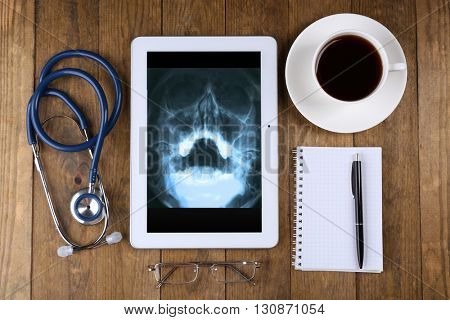 X-ray on tablet screen and stethoscope on wooden background