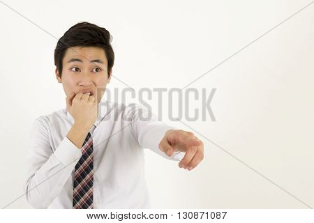 Young asian businessman covering his mouth and pointing at someone or something