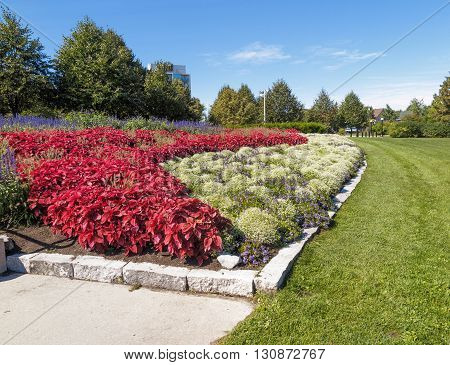 Formal flower beds in park under blue sky