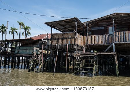 View of water front residences on Chao Phraya river in Bangkok. Curising alongisde the river banks, plenty of water front residences like this are found. Blue sky on the background looks fantastic.