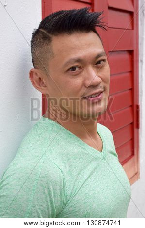 Asian Man posing outdoor besides a red window