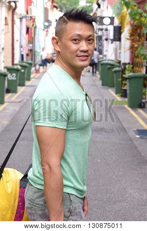 Asian Man carrying a bag posing by the road