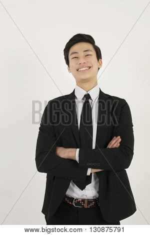 Asian young man in a black suit with his arms crossed