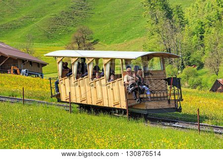 Stans, Switzerland - 8 May, 2016: people in the railcar of the Stanserhornbahn funicular railway heading upwards to the Mt. Stanserhorn. Stanserhornbahn is a funicular railway from the town of Stans to Mt. Stanserhorn established in 1891.