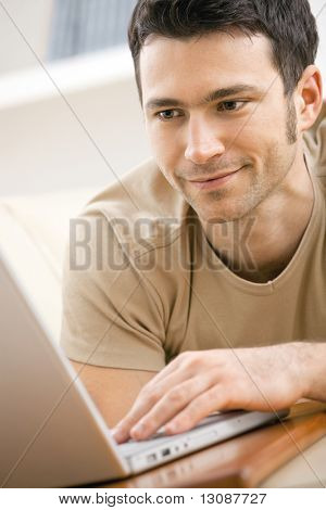 Casual man wearing beige t-shirt using laptop computer at home, looking at screen.