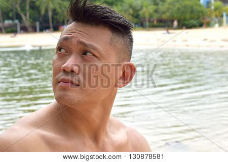 Mature Asian Man looking at the sky at the beach