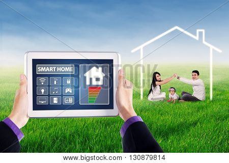 Image of digital tablet with smart home controller icons and happy family playing on the park under a house symbol