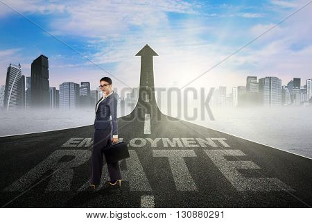 Asian businesswoman standing on the road turning into upward arrow with employment rate text
