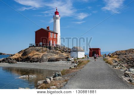 Path leading to bright white lighthouse and red tender building