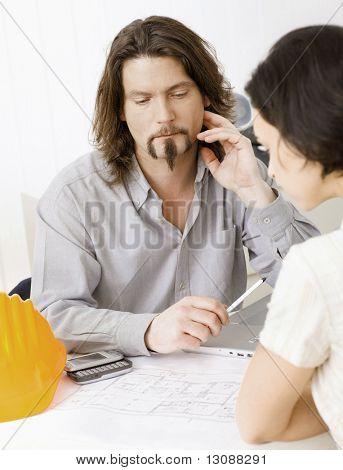 Architekt anzeigen und Pläne, weiblich Client zu erklären.