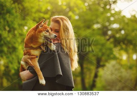 Girl and dog Shiba Inu cuddling in a spring park. Walking with a pet. Pedigree dog. Walking dogs. Dog happiness.
