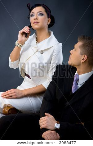 Portrait of young couple dressed in elegant clothes. Woman wearing white cocktail shirt with jacket, talink on mobile phone. Man wearing three-pieces dark suit, looking up.