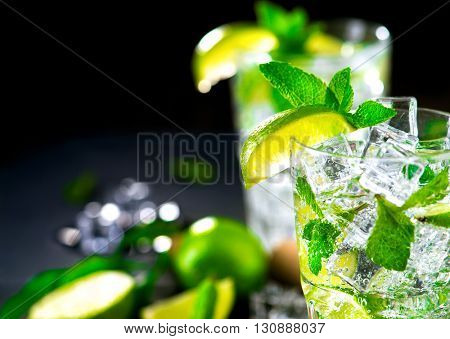 Mojito cocktail in a bur on a table in summer bar, Alcohol cocktails with Rum, lime, mint, ice cubes and brown sugar closeup, Party drink. Isolated on black background, selective focus