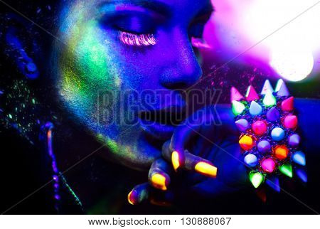 Fashion model woman in neon light, portrait of beautiful model girl with fluorescent make-up, Art design of female disco dancer posing in UV, colorful make up. Isolated on black background