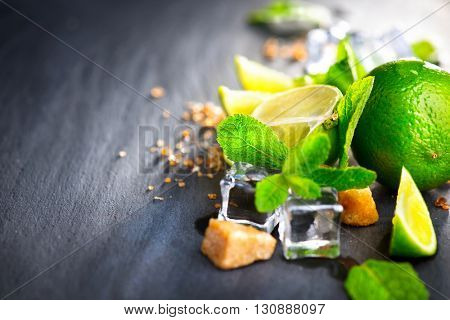 Mojito cocktail on a table in summer bar, Alcohol cocktails with Rum, lime, mint, ice cubes and brown sugar closeup, Party drink. Isolated on black background, selective focus