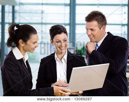 Three young businesspeople standing in lobby, looking at laptop computer screen, smiling.