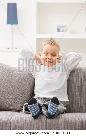 Portrait of happy 4 years old boy wearing white t-shirt, sitting at couch, looking at camera, smiling.