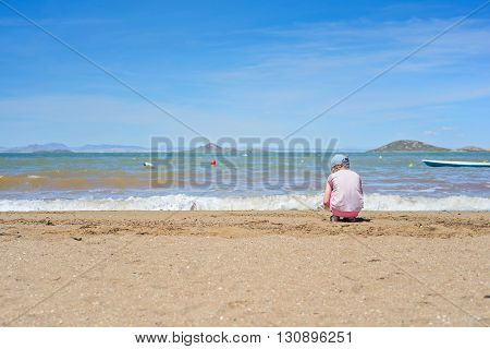 Small girl sitting and playing on the sandy Mar Menor beach, Spain