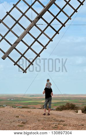 Wooden wing from old windmill over blue sky. Father and his son sitting on father's shoulders standing turned away