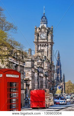 Edinburgh With Phone Booths And Red Bus Against Clocktower In Scotland, Uk