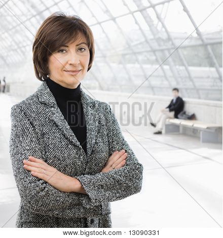 Portrait of senior businesswoman wearing grey suit, posing arms crossed in office lobby.