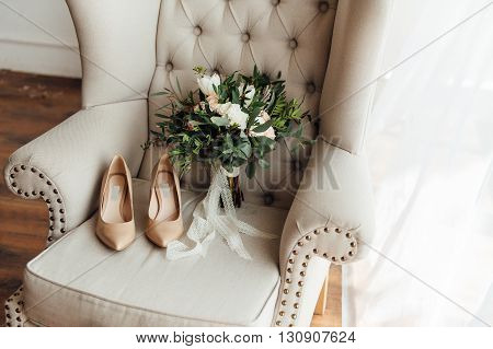 bridal bouquet of peones wedding flowers for the ceremony on the chair in a hotel room with white shoes.