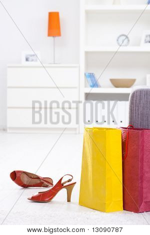 Newly bought high heel shoes on the floor beside comorful shopping bags.