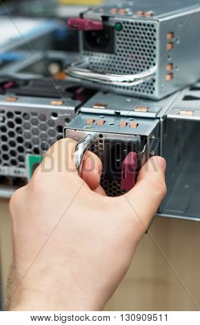 Computer Technician Installing Power Supply Unit On Server.