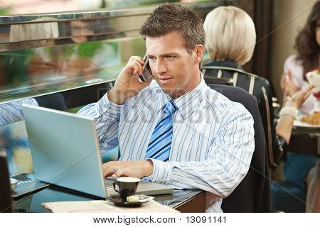 Businessman sitting at table in cafe using laptop computer, talking on mobile.