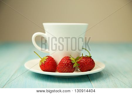 White Cup and strawberry on over blue