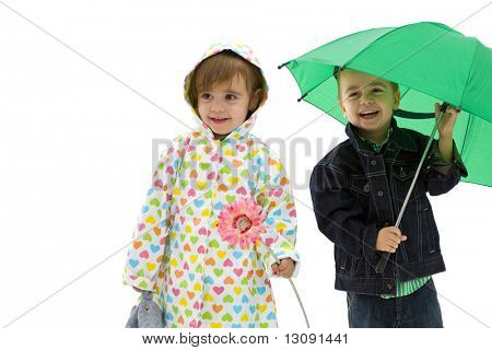 Happy laughing children. Boy holding a green umbrella. Girl wearing raincoat and holding flower. Isolated on white background.