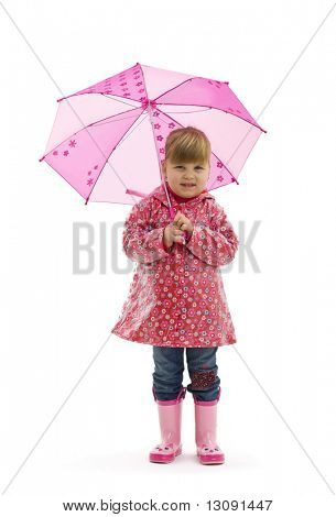 Small girl wearing raincoat with flowers and pink boots, holding pink umbrella. Isolated on white background.