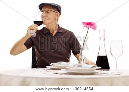 Senior gentleman holding a glass of wine and smelling the wine seated at a restaurant table isolated on white background