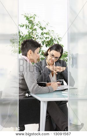 Young businesswomen sitting at office desk in modern glass office, looking at smart phone.