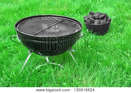 Portable Bbq Grill And Basket With Charcoal Briquettes On Lawn