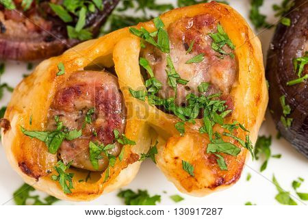 Wrapped dough sausages with onions with grilled red onions covered with minced parsley. Macro. Photo can be used as a whole background.