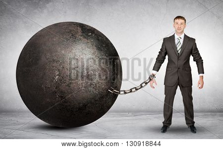 Businessman chained to large ball on grey background