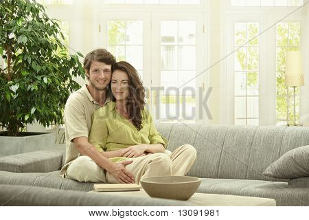Portrait of happy couple sitting together on couch, embracing. Looking at camera smiling.
