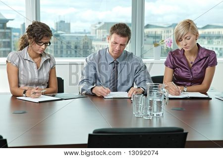 Panel of business people sitting at table in meeting room conducting job interview.