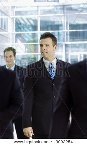 Young businessman standing among other businesspeople, in front of office building.