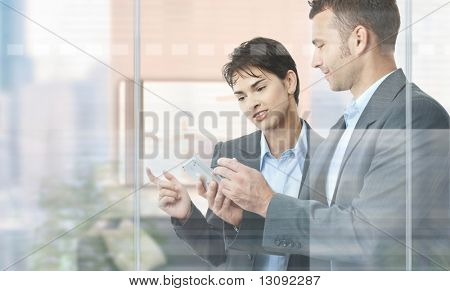 Two businesspeople standing in modern office behind glass wall, using smart mobile phone.