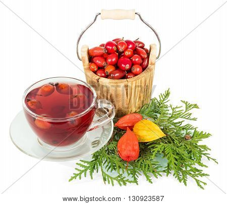 Wooden bucket with berries of wild rose and cup of tea isolated on white background.