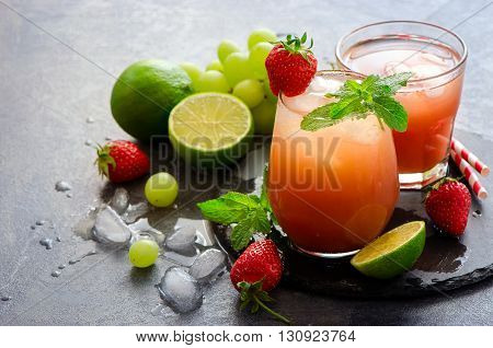 Strawberry refreshing juicy summer drink with ice cubes lime mint. Home-made lemonade lime water
