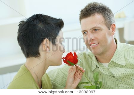 Romantic portrait of love couple. Woman smelling red rose, man smiling at her.