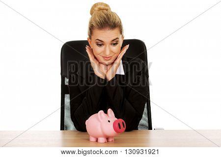 Businesswoman with a piggybank behind the desk