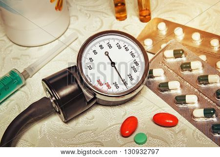 On the table is an apparatus for blood pressure measurement which shows higher pressures. It's a hypertensive crisis. Near are medications to assist.