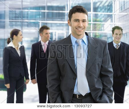 Portrait of happy businessman standing in office lounge smiling.