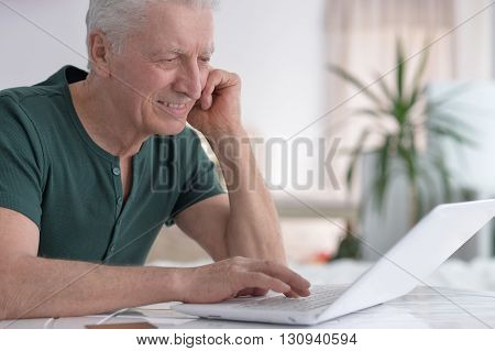 Portrait of a happy senior man using laptop