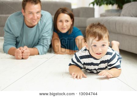 Happy family lying on floor in living room. Selective focus on little boy. poster